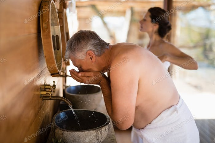 Man washing face from water in cottage