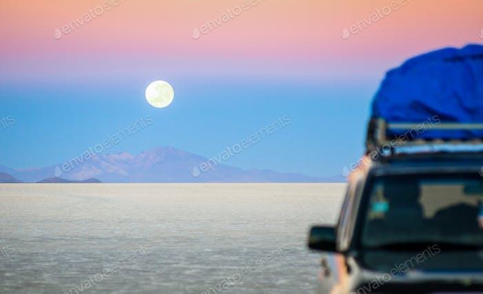 Full moon sunset with off road jeep vehicle on Salar De Uyuni