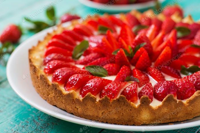 Torte mit Erdbeeren und Schlagsahne mit Minzblättern verziert.