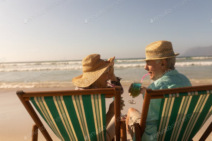 Rear view of active senior couple having cocktail drink while relaxing on sun lounger at beach