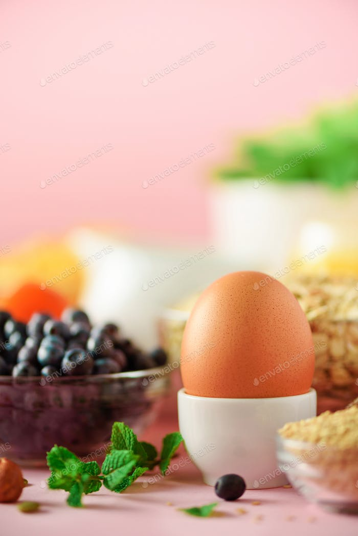 Delicious breakfast ingredients. Soft boiled egg, oat flakes, nuts, fruits, berries, milk, yogurt