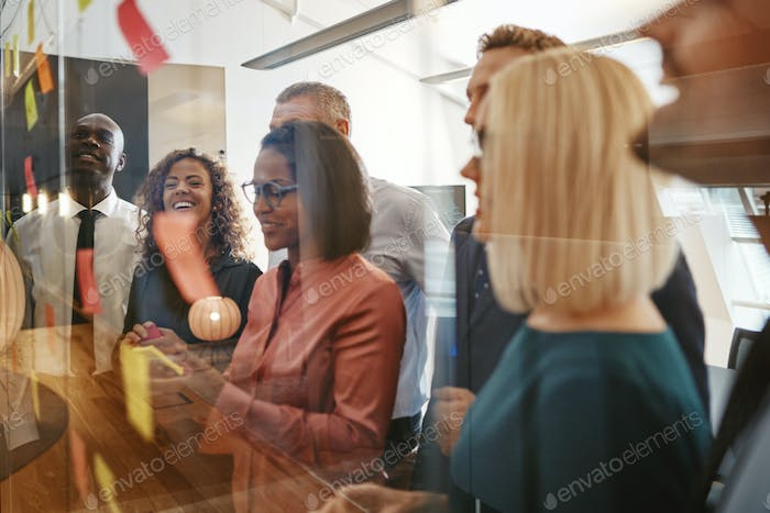 Young African businesswoman brainstorming with her team using sticky notes