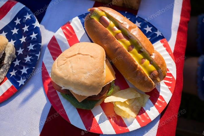 Hot Dog, Hamburger und Chips auf dem Teller serviert