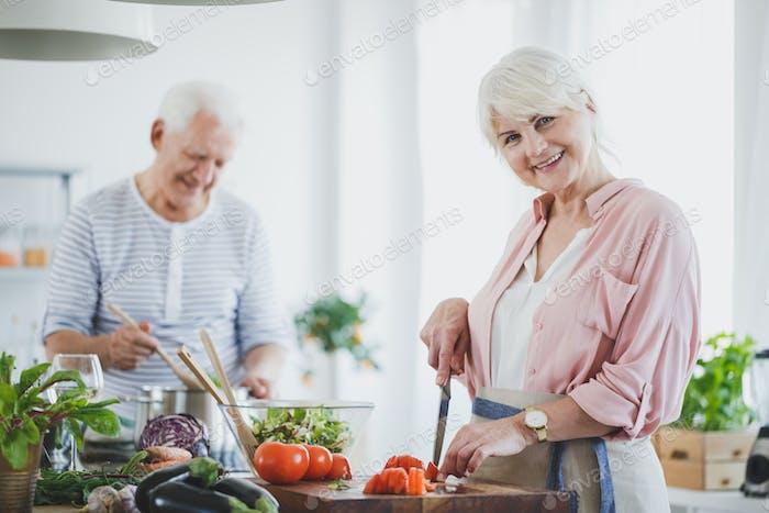 Lächelnde Senior Frau Schneiden Tomaten