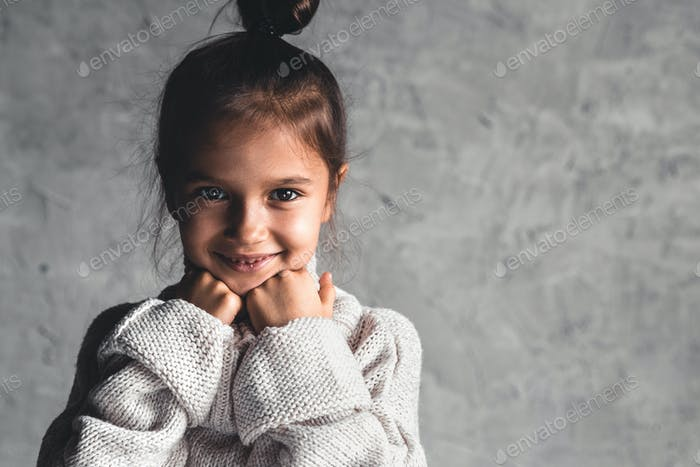 Portrait of a charming little girl in beige sweater on gray background