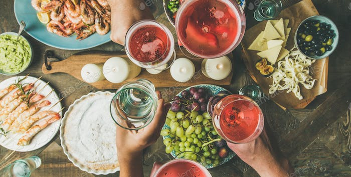 Flat-lay of friends hands eating and drinking together, wide composition