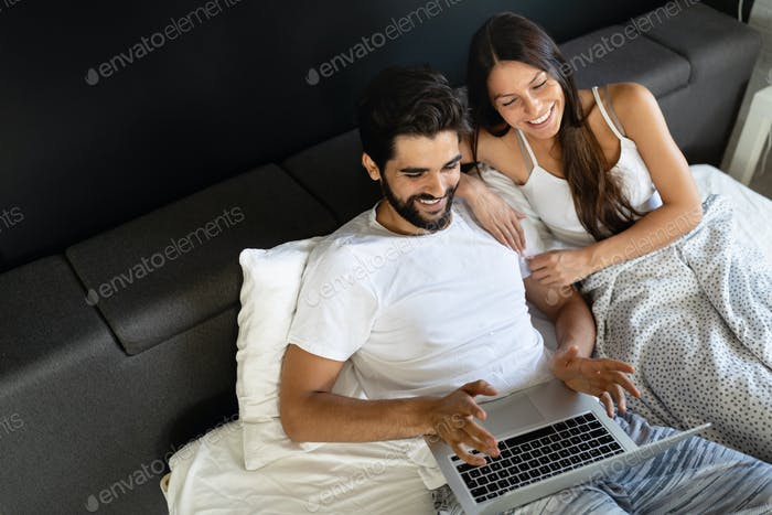 Young happy smiling couple with notebook at bedroom
