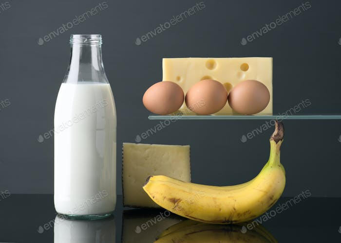 milk bottle eggs cheese and banana on gray background