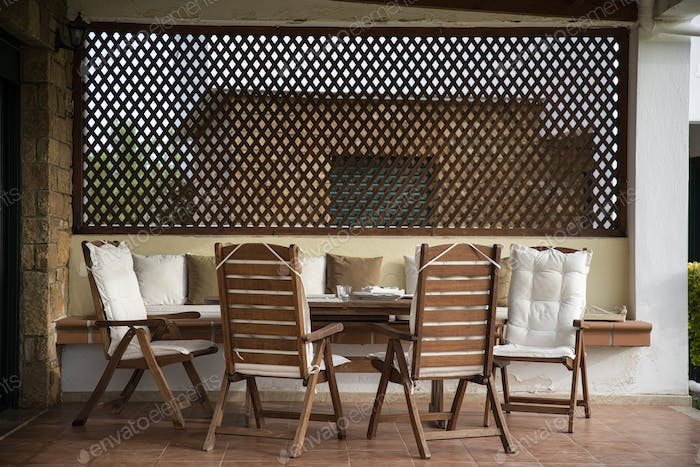 Wooden Table and Comfortable Chairs on a Porch