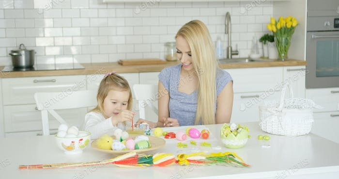 Loving mother and daughter coloring eggs
