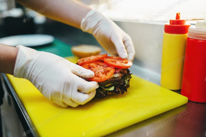 Male cook puts tomatoes in to the burger