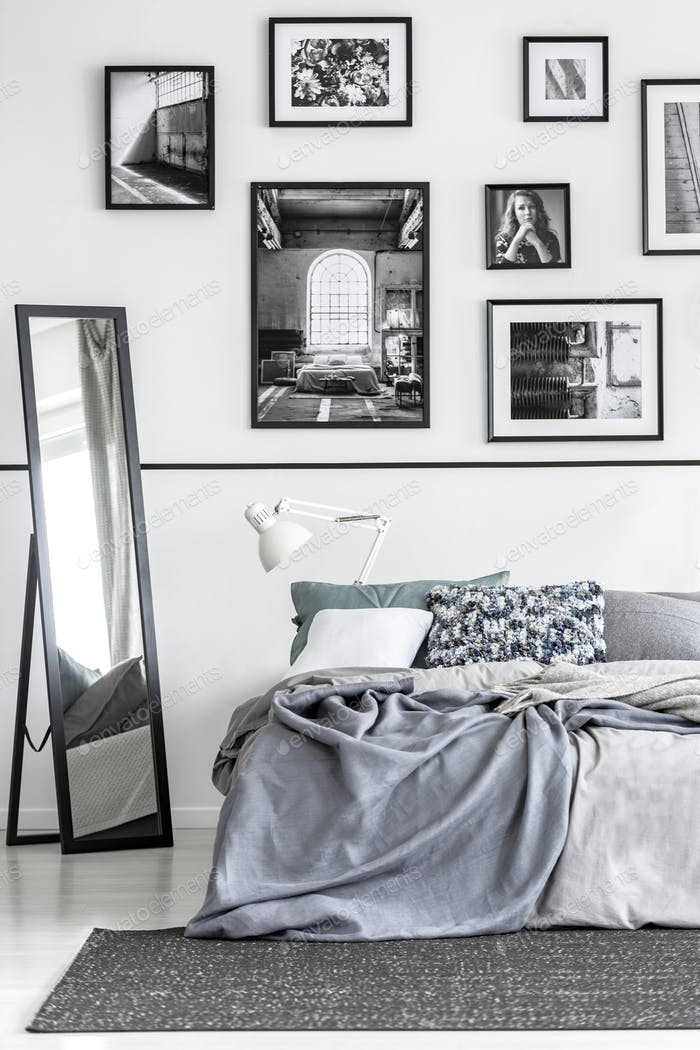 Mirror next to bed with grey sheets in white minimal bedroom int