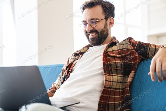 Portrait of caucasian man using laptop while sitting on sofa at home