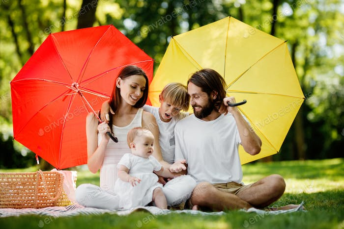 Kids and their parents sitting on the blanket under the big red and yellow umbrellas covering them