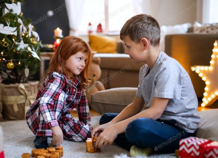Small girl and boy in pajamas indoors at home at Christmas, playing board games