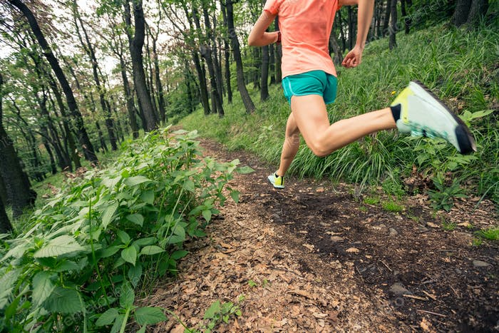 Woman trail running in green forest. Endurance sport.