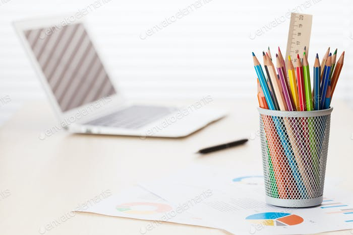 Büroarbeitsplatz mit Laptop, Berichten und Bleistiften