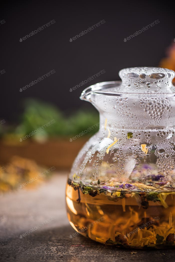 Hot aromatic herbal tea in glass kettle