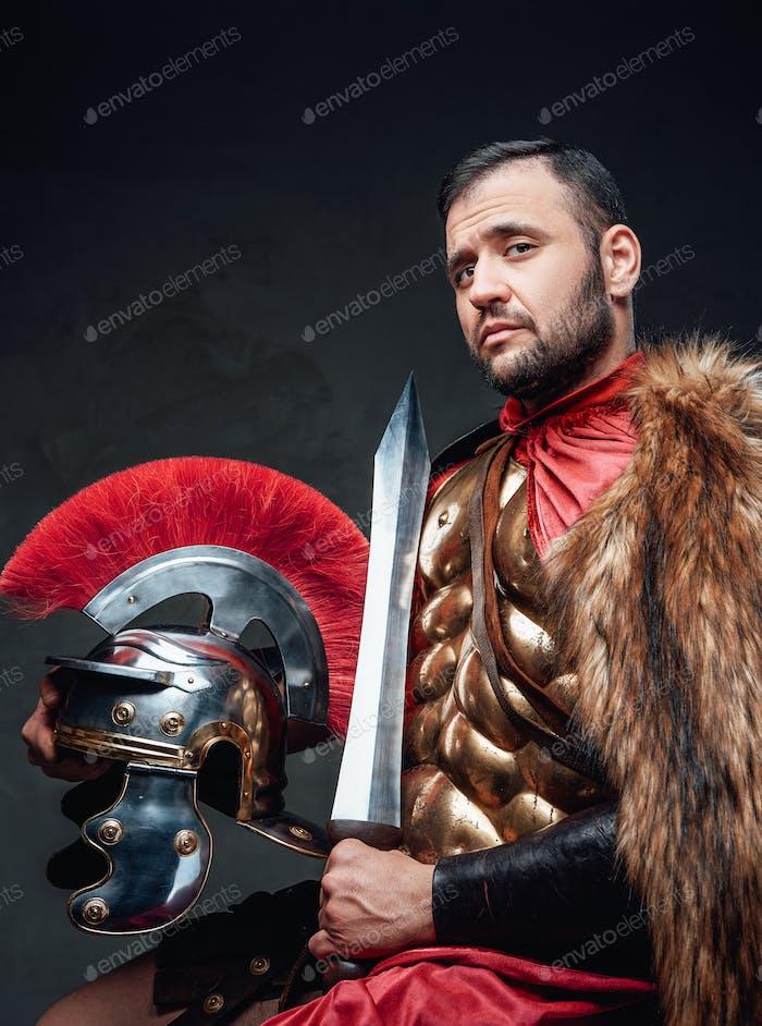 Studio shot of roman officer with sword and helmet