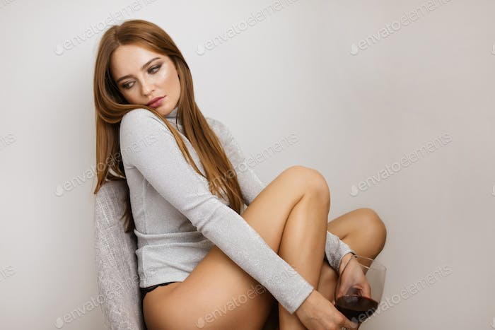 Beautiful lady sitting in chair with glass of red wine thoughtfully looking aside on gray background