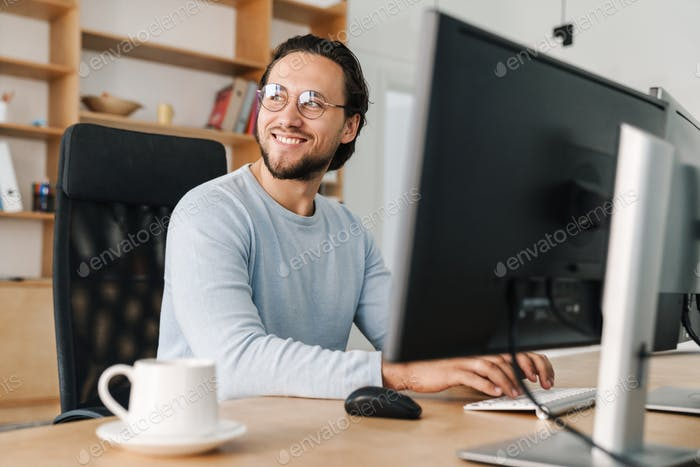 Image of smiling unshaven programmer man working with computer