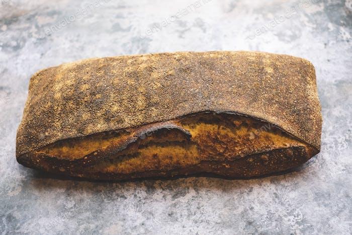 Handwerkliche Bäckerei, die spezielle Sauerteigbrot herstellt, einen gebackenen Laib mit fester dunkler Kruste.
