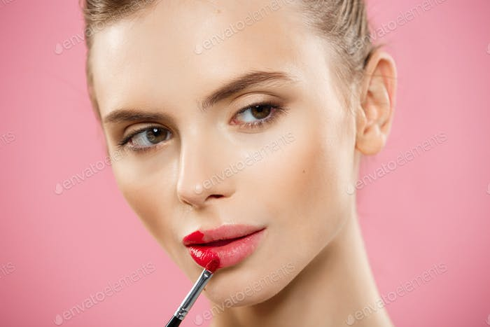 Beauty Concept - Woman applying red lipstick with pink studio background. Beautiful girl makes
