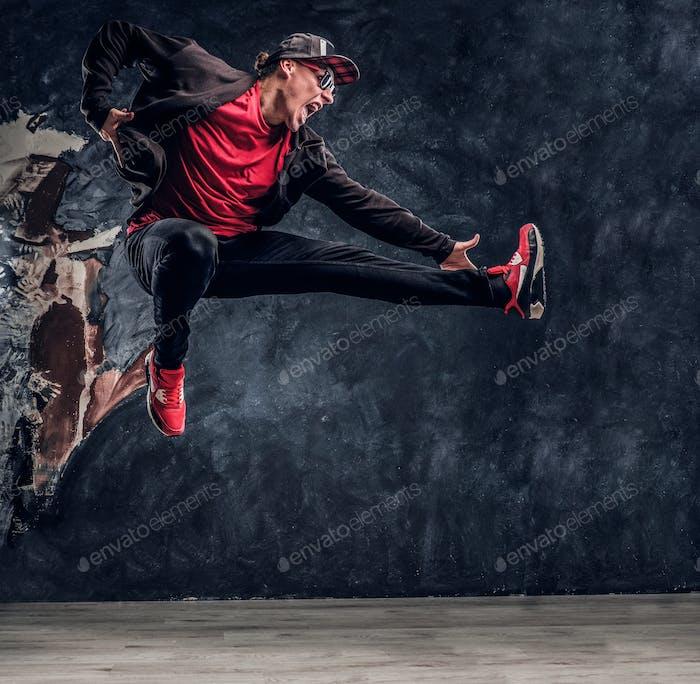 Emotional stylish dressed guy performing break dance jumping.
