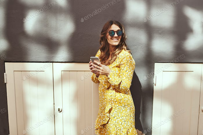 Smiling woman holding a cellphone and coffee in the city