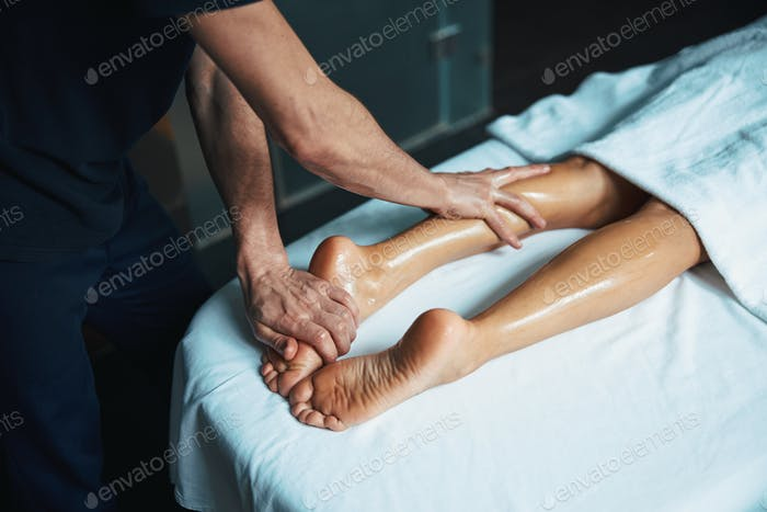 Charming young woman legs on white towel and man hands healing body treatment in beauty clinic