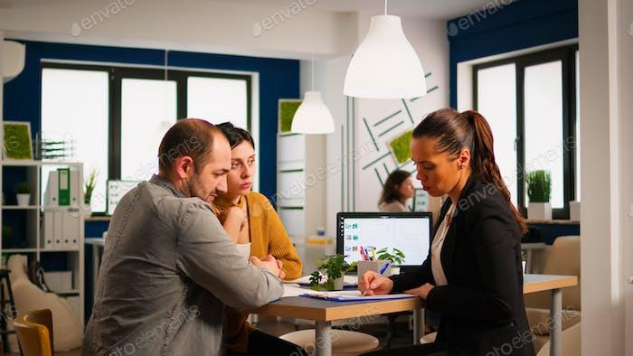 Бизнесвумен подписывает документы и консультант приветствует клиента рукопожатием