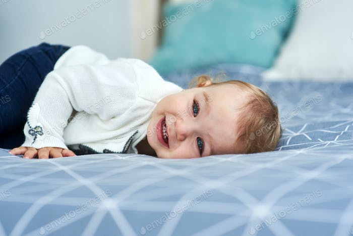 Friendly baby girl smile lying on the bed
