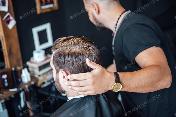 the master in the barbershop shaves and cuts the man