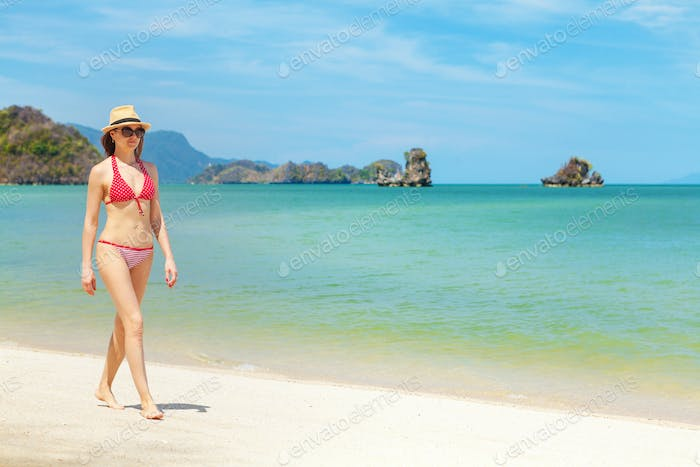 Young attractive woman walking on the sea beach