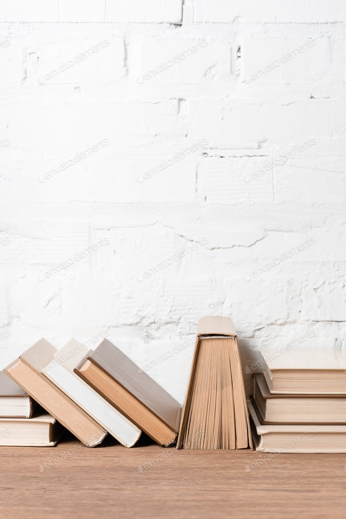 books with hardcovers on wooden table near white brick wall
