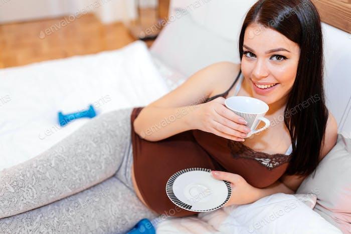 Beautiful pregnant woman drinking tea