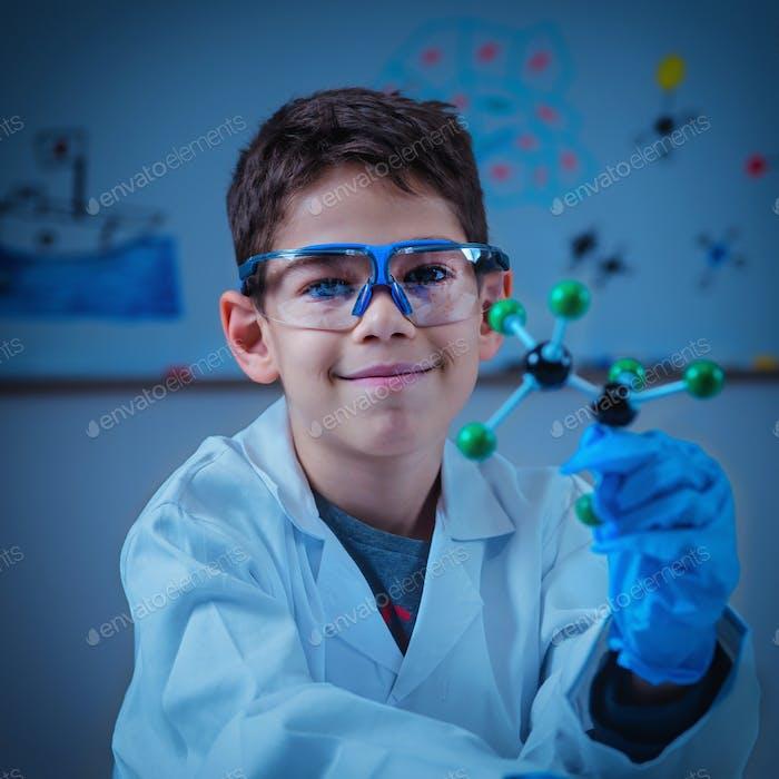 Science education. Cute boy holding molecular model