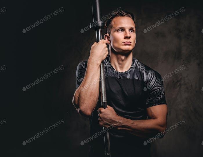 Портрет красивого молодого бодибилдера на темном фоне.