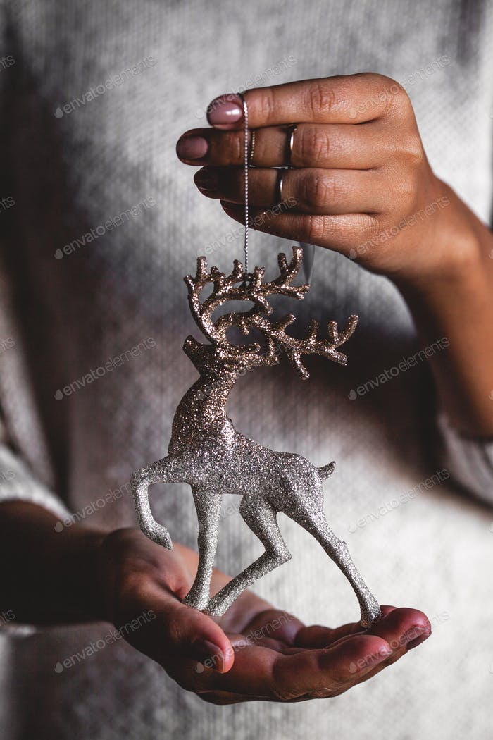 Woman in sweater holding toy deer glass decorative ball in hands, copy space. Christmas, new year