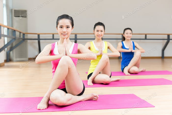 Group of young women doing exercise in aerobics class