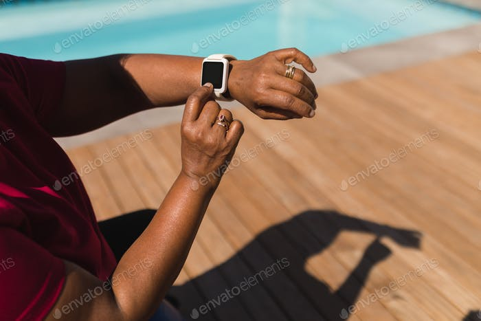 Senior woman using smartwatch next to the swimming pool in the backyard of home