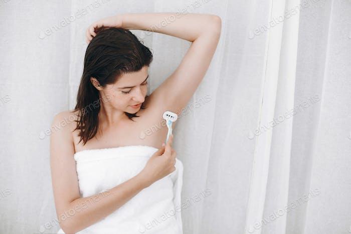 Young woman shaving armpits with plastic razor closeup