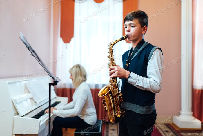 teenage boy learns to play the saxophone in a music lesson