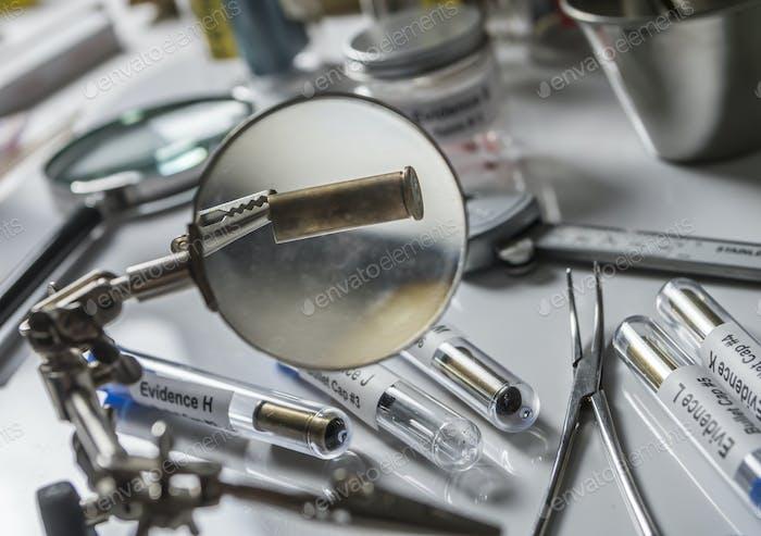 Wissenschaftliche Polizei untersucht eine Kugel Kappe im ballistischen Labor, konzeptionelles Bild