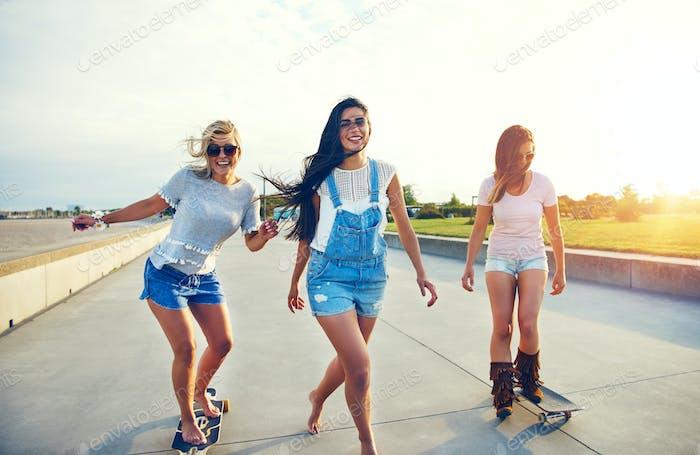 Drei junge Frau Skateboarding am Strand