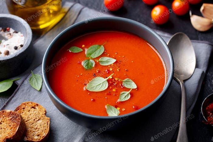 Tomato Soup with Basil in a Bowl. Dark Background. Close up.
