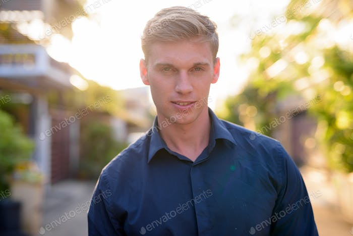 Happy young handsome businessman with blond hair smiling outdoors