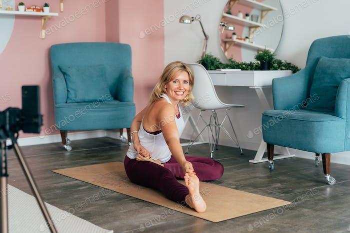 Joven bastante feliz haciendo pose de yoga para estiramiento y flexibilidad. Entrenamiento en casa.