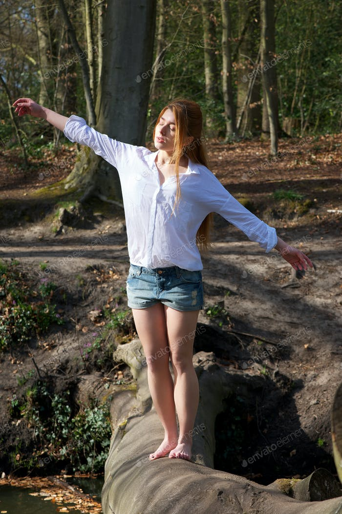 Young woman balanacing on tree trunk with arms outstretched