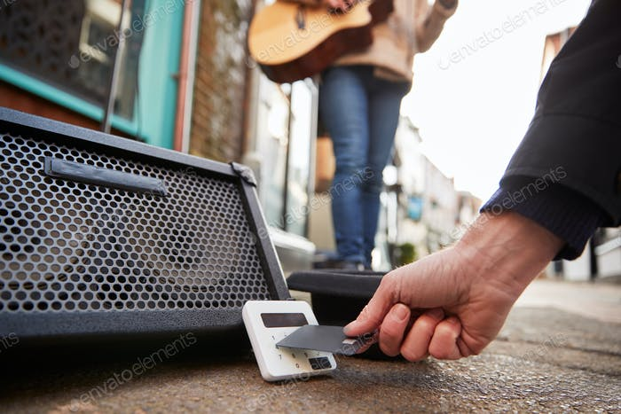 Close Up Of Person Using Contactless Payment Machine At Feet Of Female Musician Busking In Street